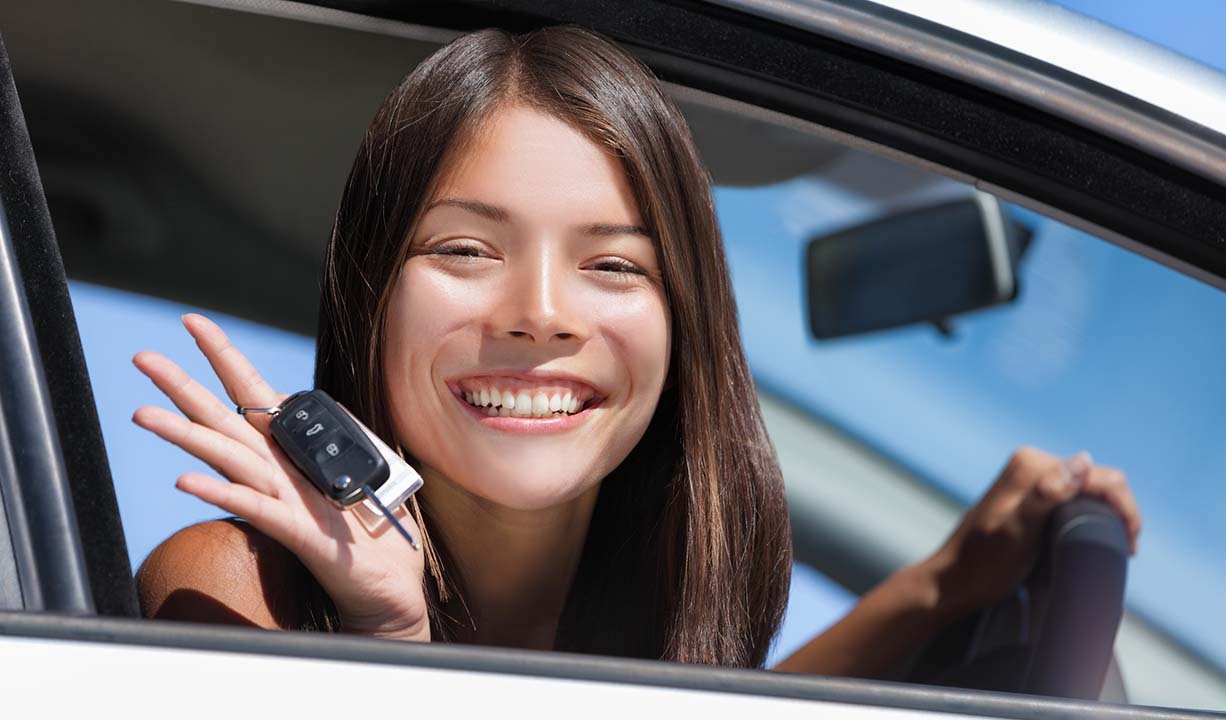 Happy Asian girl teen driver showing new car keys