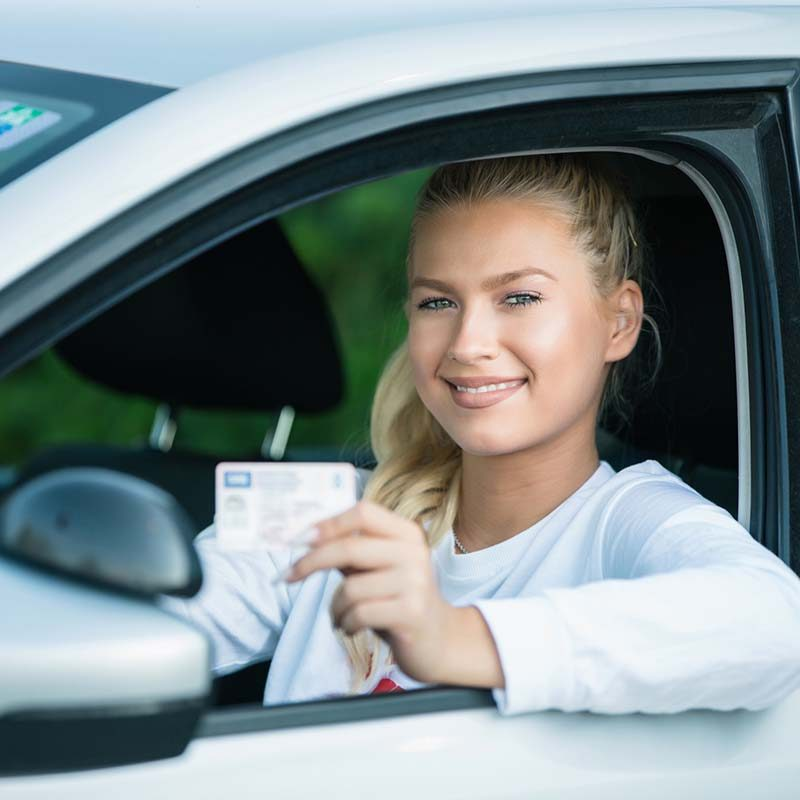 Female driving student showing drivers license